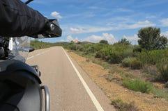 Motocicleta da equitação do motorista em uma estrada asfaltada Imagem de Stock
