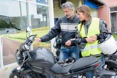 Motocicleta de explicação dos controles do homem à senhora foto de stock royalty free