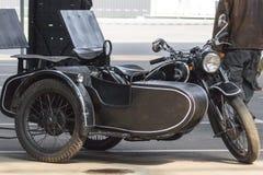 Motocicleta de três rodas velha com um side-car Izh imagem de stock