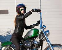 Motocicleta del montar a caballo de la mujer Chaqueta negra, casco Cierre para arriba Imágenes de archivo libres de regalías