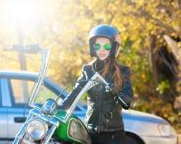 Motocicleta del montar a caballo de la mujer Chaqueta negra, casco Cierre para arriba Foto de archivo