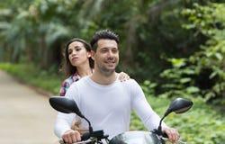 Motocicleta del montar a caballo de los pares, bici sonriente feliz Forest Exotic Vacation tropical del viaje turístico de la muj Imagenes de archivo