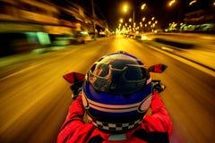 Motocicleta del montar a caballo del hombre en el camino de la noche Imagen de archivo libre de regalías