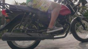 Motocicleta del montar a caballo del hombre mayor en el camino en paisaje tropical Hombre mayor en las gafas de sol que conducen  almacen de metraje de vídeo