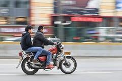 Motocicleta del ona de los hombres con las señalizaciones de la tienda en el fondo, Gaungzhou, China Imagen de archivo