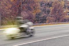 Motocicleta en el movimiento durante temporada de otoño imagenes de archivo