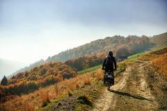 Motocicleta en un camino de tierra de la montaña en otoño Foto de archivo