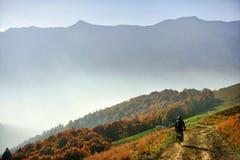 Motocicleta en un camino de tierra de la montaña en otoño Foto de archivo libre de regalías