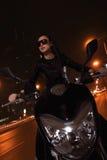 Motocicleta hermosa del montar a caballo de la mujer joven en gafas de sol a través de las calles de la ciudad en la noche Fotografía de archivo