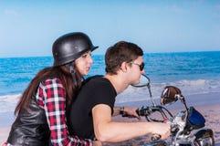 Motocicleta joven del montar a caballo de los pares en la playa Imagen de archivo