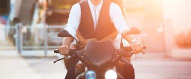 Motocicleta joven del ridind de los pares en la puesta del sol en ciudad imagenes de archivo