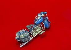 Motocicleta miniatura en fondo rojo fotografía de archivo
