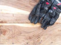 Motocicleta negra de los guantes en la tabla de madera Foto de archivo libre de regalías