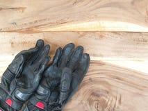 Motocicleta negra de los guantes en la tabla de madera vieja Imágenes de archivo libres de regalías