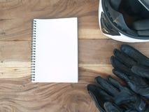 Motocicleta negra de los guantes y libro blanco del casco y blanco en la madera Fotos de archivo libres de regalías
