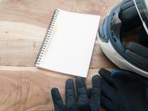Motocicleta negra de los guantes y libro blanco del casco y blanco en la madera Imagen de archivo