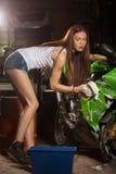 Motocicleta que se lava de la mujer Imagenes de archivo