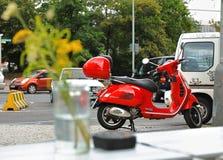 Motocicleta roja parqueada de la vespa en una selva urbana foto de archivo