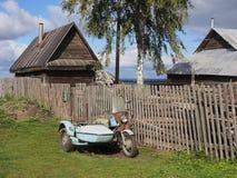 Motocicleta velha com o side-car perto da cerca Campo Rússia Foto de Stock Royalty Free