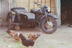 Motocicleta velha com o side-car que está em uma jarda rural fotografia de stock