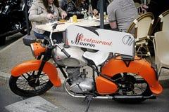 Motocicleta vieja usando puerta del menú en un restaurante Fotos de archivo