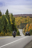 Motocicleta y coches que viajan en un camino en otoño Foto de archivo
