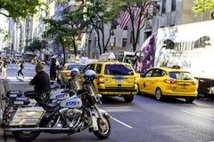 Motocicletas de la policía de Nueva York y taxis amarillos en las calles de Manhattan foto de archivo