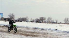 Motocicletas, jinete de los motoristas de los niños en pista nevosa del motocrós Jinete en nieve Jinete en la bici, invierno del  metrajes