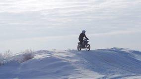 Motocicletas, jinete de los motoristas de los niños en pista nevosa del motocrós Jinete en nieve Jinete en la bici, invierno del  almacen de metraje de vídeo