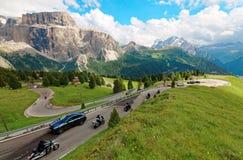 Motocicletas y coches que viajan con una vuelta aguda de una bobina de la carretera en las colinas de Sella rugoso fotografía de archivo