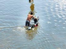 Motocicletta dei sacchetti dell'uomo attraverso acqua Immagini Stock Libere da Diritti