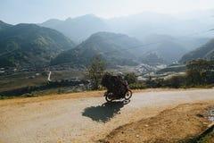motocicletta di guida della persona e legno di trasporto sulla strada della montagna, PA del Sa, Vietnam Fotografie Stock