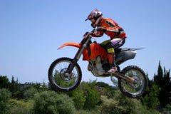 Motocicletta di Moto X che salta attraverso l'aria un giorno pieno di sole caldo con cielo blu Immagine Stock Libera da Diritti