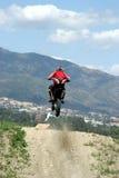 Motocicletta di Moto X che salta attraverso l'aria un giorno pieno di sole caldo con grande cielo blu Immagine Stock