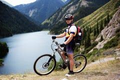 Motociclista ao lado do lago da montanha imagem de stock