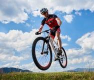Motociclista atlético do desportista no voo profissional do sportswear no ar em sua bicicleta no céu azul brilhante fotografia de stock royalty free
