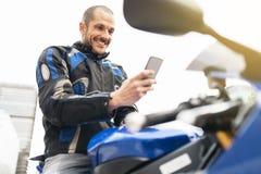 Motociclista bello che per mezzo del telefono cellulare Fotografie Stock