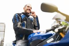 Motociclista bello che per mezzo del telefono cellulare Immagini Stock