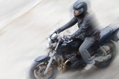 Motociclista in casco e guida nera del rivestimento sulla strada Immagine Stock Libera da Diritti