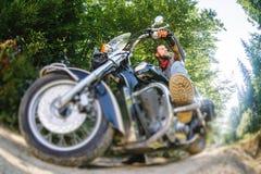 Motociclista che conduce il suo motociclo dell'incrociatore sulla strada nella foresta immagini stock