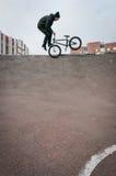 Motociclista che fa trucco del tailwhip del footjam Immagine Stock