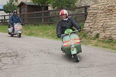 Motociclista che guida una vespa d'annata del motorino Fotografia Stock