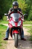 Motociclista che si leva in piedi sulla strada campestre Immagini Stock