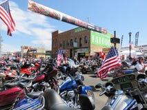 Motociclista com as bandeiras americanas nas cerimônias de inauguração na rua aglomerada, Sturgis do centro, SD Fotografia de Stock Royalty Free