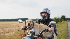 Motociclista com um cão que senta-se em uma motocicleta fora video estoque