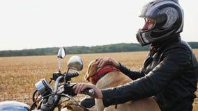 Motociclista com um cão que senta-se em uma motocicleta fora filme