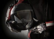 Motociclista con il casco in sue mani. Fondo scuro Fotografia Stock Libera da Diritti