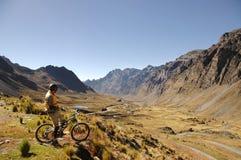 Motociclista da montanha que olha o vale fotografia de stock