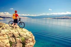 Motociclista da montanha que olha a vista e que monta uma bicicleta imagens de stock