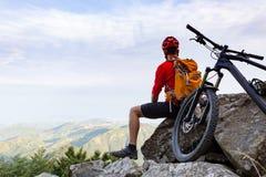 Motociclista da montanha que olha a vista na fuga da bicicleta em montanhas do outono Imagens de Stock Royalty Free